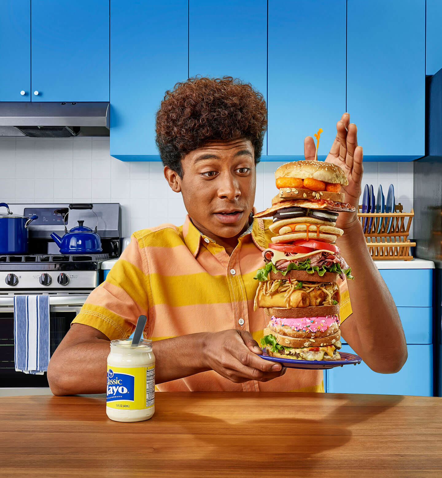 Man in a kitchen about to eat an incredibly large sandwich.